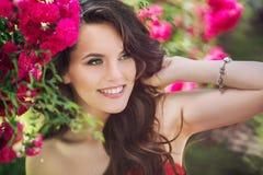 Junge Frau mit einer rosa Blume Sommerschuß im Freien Stockbild