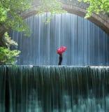 Junge Frau mit einer roten Regenschirmstellung und -blicken auf den Wasserfall Lizenzfreie Stockbilder