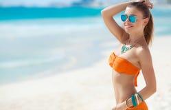 Junge Frau mit einer schönen Zahl auf einem tropischen Strand stockbilder