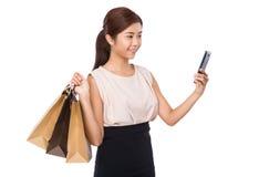 Junge Frau mit Einkaufstasche und der Anwendung des Handys Stockfoto