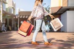 Junge Frau mit Einkaufstaschen am Einkaufszentrum stockbilder