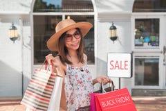 Junge Frau mit Einkaufstaschen am Einkaufszentrum an schwarzem Freitag, Frauenlebensstilkonzept stockfoto