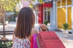 Junge Frau mit Einkaufstaschen am Einkaufszentrum an schwarzem Freitag, Frauenlebensstilkonzept lizenzfreie stockfotos