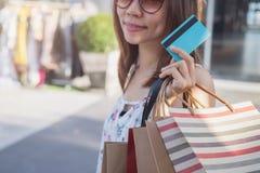 Junge Frau mit Einkaufstaschen und Kreditkarte am Einkaufszentrum stockbild