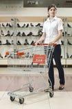 Junge Frau mit Einkaufswagen lizenzfreie stockfotografie