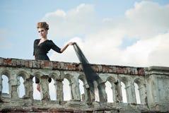 Junge Frau mit elegantem Kleid auf Terrasse lizenzfreies stockbild