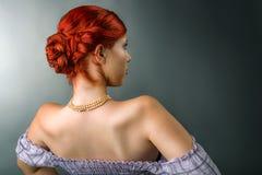 Junge Frau mit eleganter umsponnener Frisur und Berufsmake-up Stockfoto