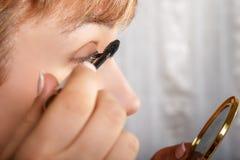 Junge Frau mit Eyeliner für ihre Wimpern lizenzfreie stockfotografie