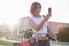 Junge Frau mit Fahrfahrrad in der Stadt Schauen des intelligenten Telefons mit Lizenzfreie Stockbilder