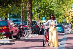 Junge Frau mit Fahrrad auf europäischen Ferien in Amsterdam Lizenzfreies Stockfoto