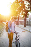 Junge Frau mit Fahrrad bei Sonnenuntergang stockfotografie