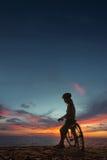 Junge Frau mit Fahrrad am Seestrand Stockbilder