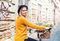 Junge Frau mit Fahrrad und Blumen in der sonnigen Frühlingsstadt Lizenzfreie Stockbilder