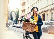 Junge Frau mit Fahrrad und Blumen in der sonnigen Frühlingsstadt Stockfotografie