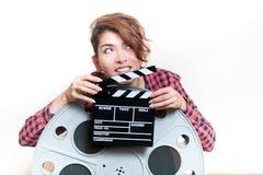 Junge Frau mit Filmscharnierventil hinter großer Kinospule Stockfotografie