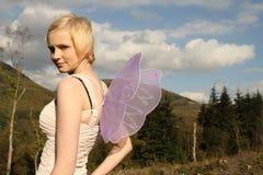 Junge Frau mit Flügeln gegen hellen blauen Himmel Stockbild