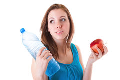 Junge Frau mit Flasche des Wassers und des Apfels Lizenzfreie Stockfotografie