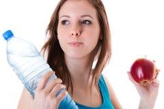 Junge Frau mit Flasche des Wassers und des Apfels Stockbilder