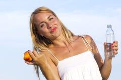 Junge Frau mit Flasche und Frucht in der Hand Lizenzfreies Stockbild