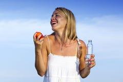 Junge Frau mit Flasche und Frucht in der Hand lizenzfreie stockfotos