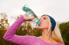 Junge Frau mit Flasche Wasser Lizenzfreie Stockbilder