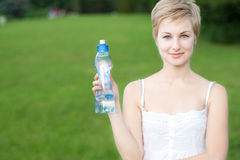 Junge Frau mit Flasche Wasser draußen Stockfoto