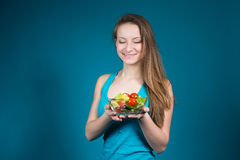 Junge Frau mit frischem Salat auf blauem Hintergrund. Lizenzfreies Stockfoto