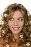 Junge Frau mit Gänseblümchen im gelockten Haar schaut weg Lizenzfreie Stockfotografie