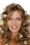 Junge Frau mit Gänseblümchen im Haar und in den Zähnen Lizenzfreie Stockfotografie
