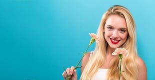 Junge Frau mit Gartennelke lizenzfreie stockbilder