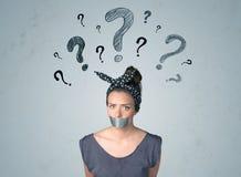 Junge Frau mit geklebtem Mund und Fragezeichensymbolen Stockfoto