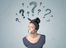 Junge Frau mit geklebtem Mund und Fragezeichensymbolen Stockfotos
