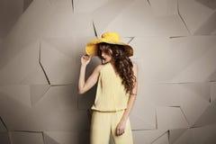 Junge Frau mit gelockter Frisur im gelben Hut und im Overall auf grauem grafischem Hintergrund Lizenzfreies Stockbild