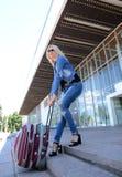 Junge Frau mit Gepäck auf den Schritten Lizenzfreies Stockfoto