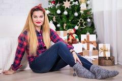 Junge Frau mit Geschenkboxen und verziertem Weihnachtsbaum Stockbilder