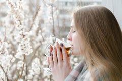 Junge Frau mit geschlossenen Augen trinken einen Tee Genießen des Frühlinges Stockfoto