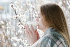 Junge Frau mit geschlossenen Augen trinken einen Tee Genießen des Frühlinges Stockbild