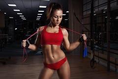 Junge Frau, mit gesunder sportlicher Zahl mit Springseil in der Turnhalle Stockfoto