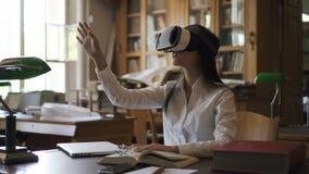 Junge Frau mit Gläsern der virtuellen Realität auf dem Gesicht, sitzend in der Bibliothek stock video footage