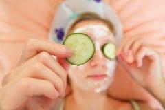 Junge Frau mit Gurkenscheiben auf dem Gesicht in einem Badekurortsaal Lizenzfreies Stockfoto
