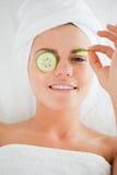 Junge Frau mit Gurkescheiben auf dem Gesicht Stockfotografie