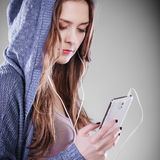 Junge Frau mit hörender Musik des intelligenten Telefons Lizenzfreies Stockfoto
