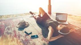 Junge Frau mit hörender Musik des Laptops mit Kopfhörern nahe dem Ozean Stockfoto