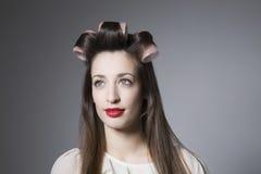 Junge Frau mit Haar-Rollen und rotem Lippenstift Stockfoto