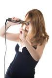 Junge Frau mit Haarstrecker Stockfotografie
