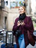 Junge Frau mit Handy draußen Stockfoto