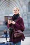 Junge Frau mit Handy draußen Stockfotografie