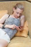Junge Frau mit Handy im Wohnzimmer Stockfotos