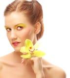 Junge Frau mit hellem bilden das Halten der Orchidee Lizenzfreie Stockfotos