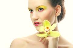Junge Frau mit hellem bilden das Halten der Orchidee Lizenzfreies Stockbild